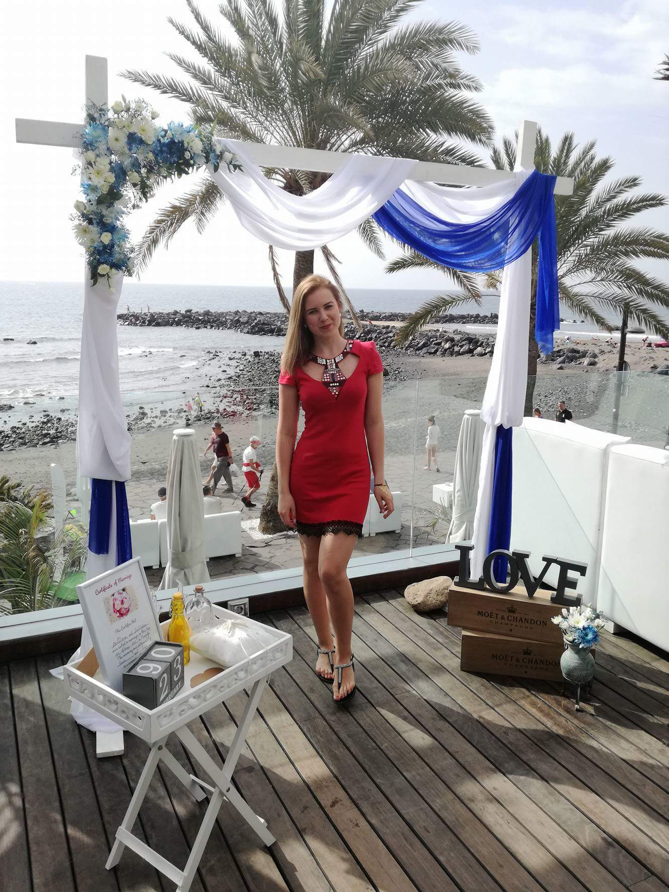 A girl with a red dress standing before the start of the wedding